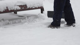 Janitor cleans the yard with shovel after heavy snowfall Footage