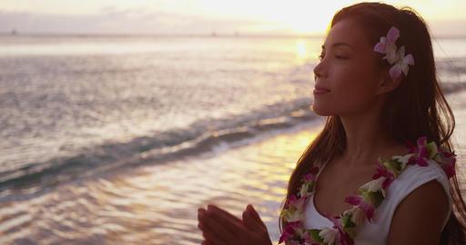 Spiritual - woman giving namaste gesture yoga meditation on Hawaii wearing lei Live Action