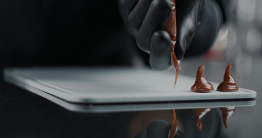 Chef chocolatier makes sweets from melted chocolate with pastry bag in slow Live Action