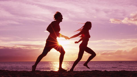 Beach couple running having fun holding hands on beach enjoying romantic sunset Live Action