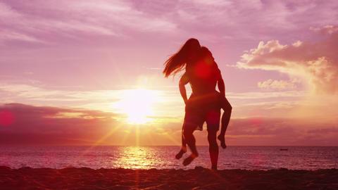 Couple piggybacking on beach having fun enjoying sunset on honeymoon travel Live Action