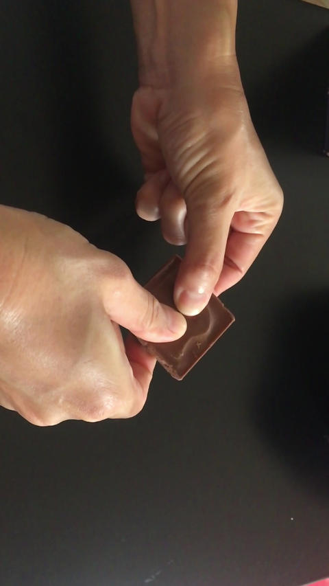 Slow motion hand on chocolate bar Live Action