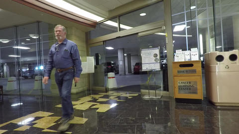 Cancer hospital man entering from parking garage HD 895 Footage