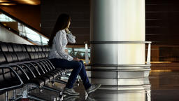 Excited woman talk on phone sit in airport loungs, say goodbye and finish call Footage