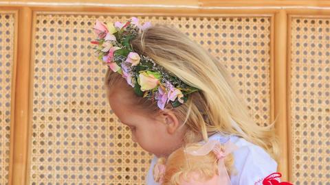 Closeup Little Blond Girl in Garland Chews Candy Footage