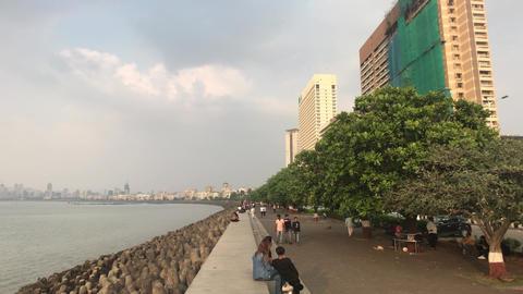 Mumbai, India - November 10, 2019: Marine Drive tourists walk along the Live Action