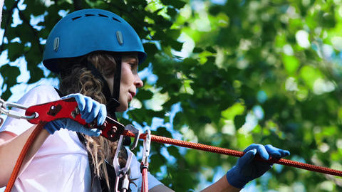 Extreme rope adventure in the park - woman in blue gloves carefully walks Live Action