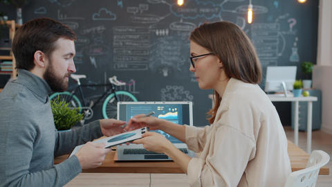 Businesswoman talking to colleague discussing information in charts and graphs Live Action