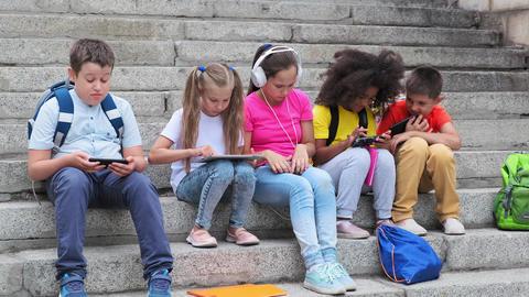 schoolchildren use gadgets resting on steps after lessons Live Action