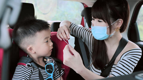 family with children rides in car and mother help child wear medical mask Live Action