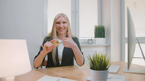 Happy female with bitcoin showing thumbs up. Smiling cheerful blond woman in Live Action