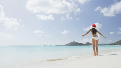 Christmas beach girl in santa hat jumping having fun on vacation Live Action