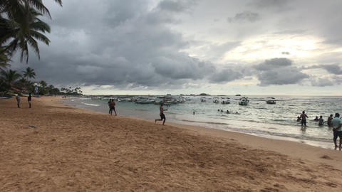 Hikkaduwa, Sri Lanka, palm trees and beach in bad weather Live Action