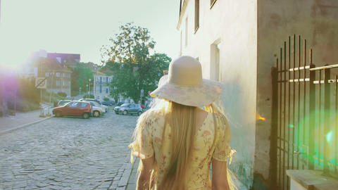 Smiling girl walking on town street. Smiling woman looking back at camera while Live Action