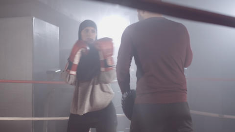 Positive muslim woman and Caucasian man training in haze on boxing ring Live Action