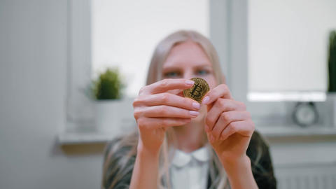 Woman studying bitcoin in hands. Close-up view of hands of young blond female in Live Action