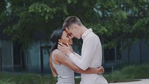 Mixed-race adults in love snuggling by foreheads to each other in park Live Action