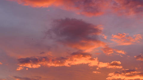 Clouds colored by the setting sun move through the evening sky Live Action