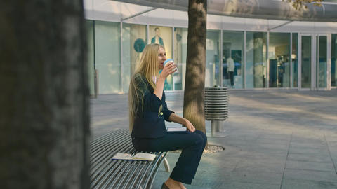 Woman with coffee and tablet on bench. Side view of formal young woman sitting Live Action