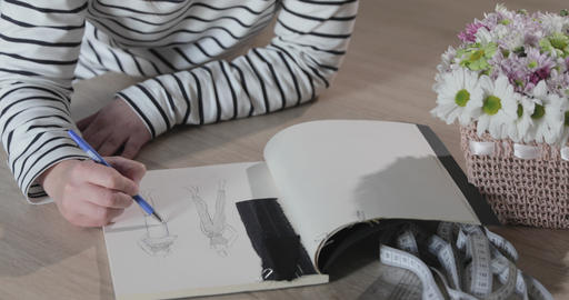 Slow motion video of the girl draws the sketch of future model of clothes in the Live Action