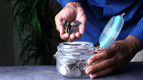 Close up of man saving coins in a jar Live Action