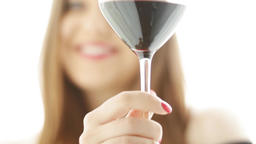 Happy young woman tasting and enjoying a glass of red wine, girl smiling and Live Action