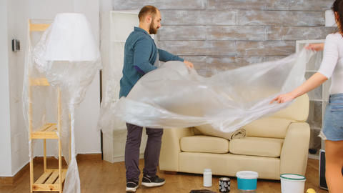 Couple wrapping sofa in plastic foil Live Action
