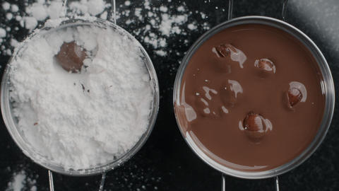 Tabletop shot: chef chocolatier drops truffles to the sugar powder in slow Live Action