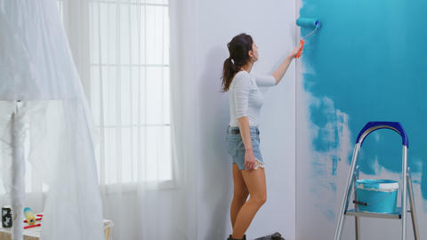 Adult woman painting wall Live Action