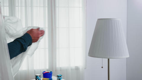 Man covering lamp with plastic sheet Live Action