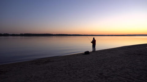 A man is fishing at sunrise by the river. The yellow sun rises from the horizon Live Action