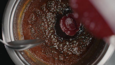 Tabletop slow motion video: chef adds mashed strawberriy to the boiling caramel Live Action