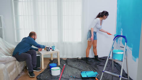 Wife painting wall with roller brush Live Action