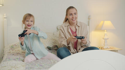 Joyful woman and little girl playing video game celebrating victory having fun Live Action