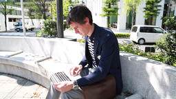 Caucasian businessman working outdoors with laptop in Tokyo, Japan Footage