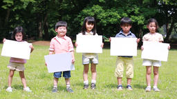 Japanese kids with whiteboards in a park, Tokyo, Japan Filmmaterial