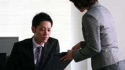 Japanese business people consulting about documents in the office Footage