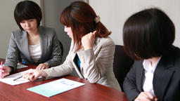 Japanese businesswomen having a meeting at a wooden desk in a modern meeting roo Footage