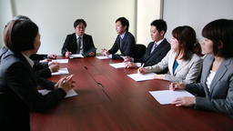 Japanese business people having a meeting around a wooden desk in a modern meeti GIF