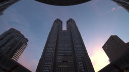 Time-lapse day to night pan up view of Tokyo Metropolitan Office Building in Shi Footage