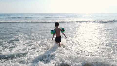 Happy child son with water wing walking to sea horizon over waves splash,summer Live Action