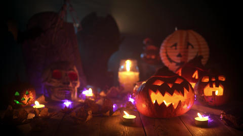 Still life of pumpkins, candles and other halloween attributes at the table Live Action