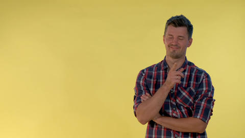 On yellow background cheerful tall boy making a hush gesture Live Action