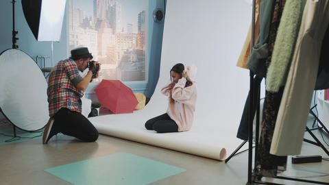 In well-equipped studio photo shoot young photographer taking photos of Live Action