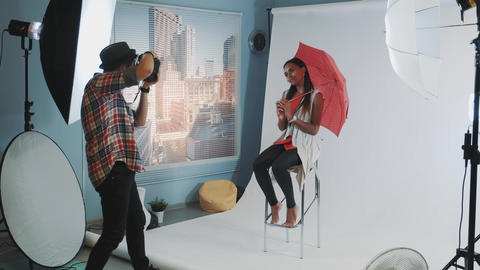 Stylish african model posing with red umbrella on bar high chair for fashion Live Action