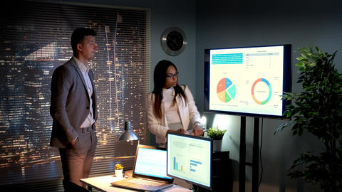 Business man and business woman analyzing company growth depicted on infographic Live Action
