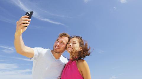People having fun - couple taking smart phone selfie Live Action