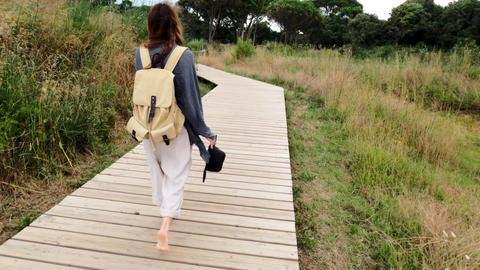 Hiking. A girl with a backpack walks on a coastal path. A girl with long hair is Live Action