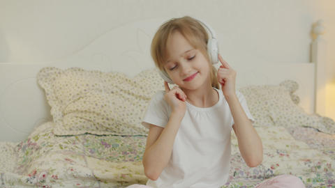 Happy kid enjoying music in headphones moving head relaxing on bed in apartment Live Action