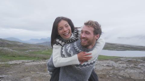 Couple doing piggyback having fun laughing joyful Live Action